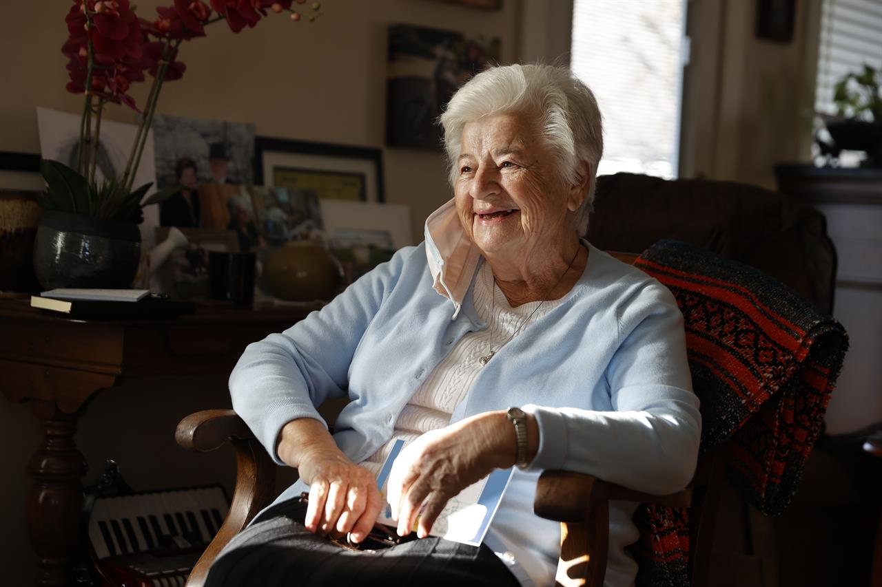 FILE - In this Nov. 12, 2020 file photo, Marjan Martin Curtis poses at her home in Spanish Fork, Utah. The 79-year-old widow, who has Stage 4 cancer, formed a fast and unlikely friendship with Amy Baird after Baird spotted Curtis' gorgeous gardening efforts along a nearby county road. (AP Photo/Jeff Swinger)