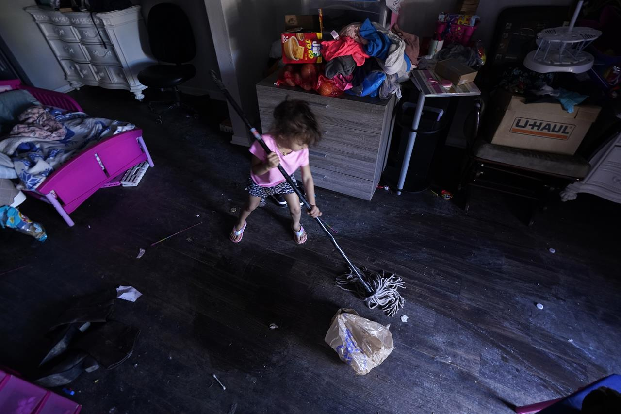 Raella Mills, 3, plays mop-up at her home Tuesday, Feb. 23, 2021, in Dallas. Raella and her mother's apartment flooded last week by a pipe that burst during the record winter cold. They are still without running water. (AP Photo/LM Otero)