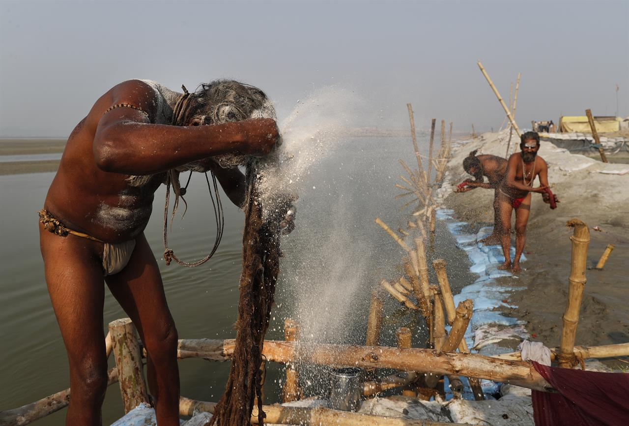 A Hindu Holy man smears ash on his hair after a holy dip at Sangam, the sacred confluence of the rivers Ganga, Yamuna and the mythical Saraswati, during Magh Mela festival, in Prayagraj, India. Tuesday, Feb. 16, 2021. Hindus believe that ritual bathing on auspicious days can cleanse them of all sins. A tented city for the religious leaders and the believers has come up at the sprawling festival site with mounted police personnel keeping a close watch on the activities. The festival is being held amid rising COVID-19 cases in some parts of India after months of a steady nationwide decline. (AP Photo/Rajesh Kumar Singh)