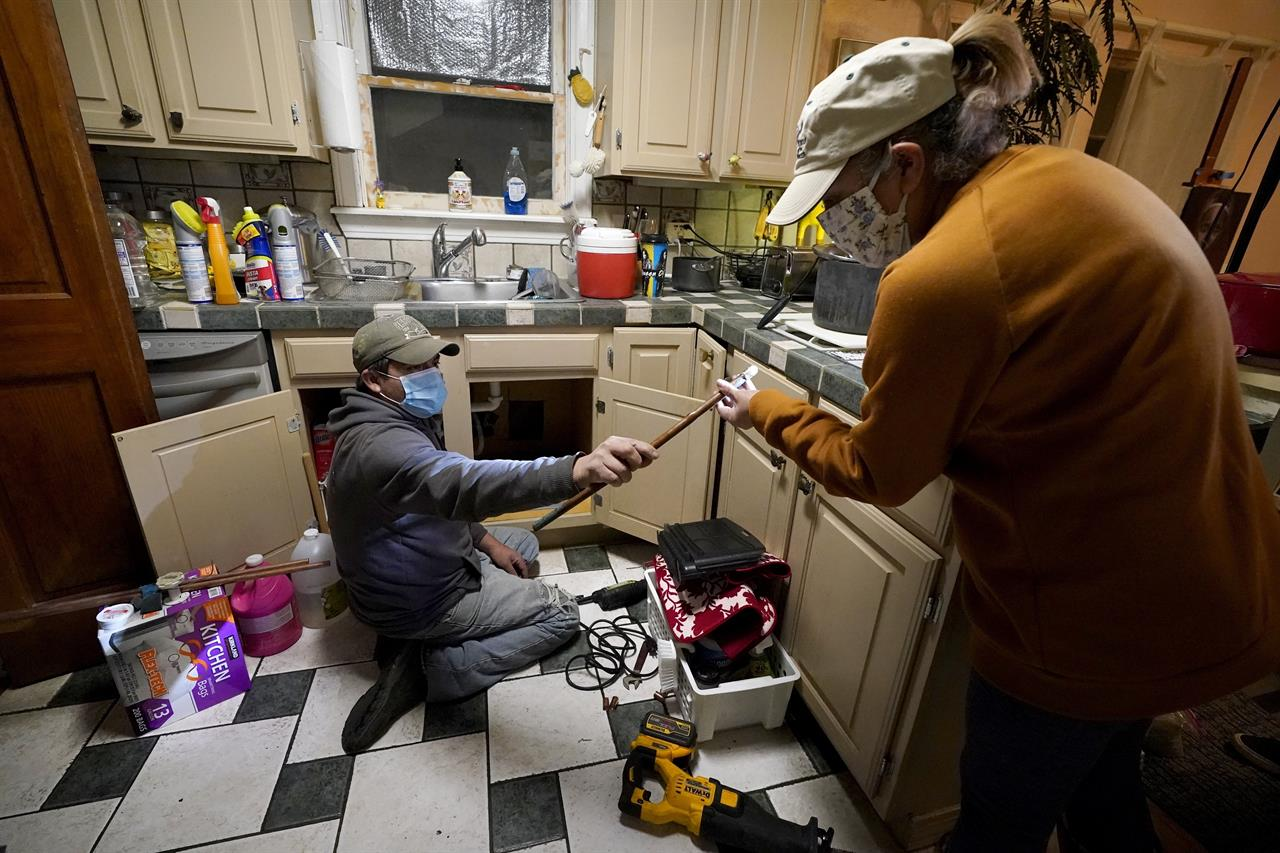 FILE - In this Feb. 20, 2021, file photo, Handyman Roberto Valerio, left, hands homeowner Nora Espinoza the broken pipe after removing it from beneath her kitchen sink in Dallas. The pipe broke during freezing temperatures brought by last week's winter weather. (AP Photo/Tony Gutierrez, File)