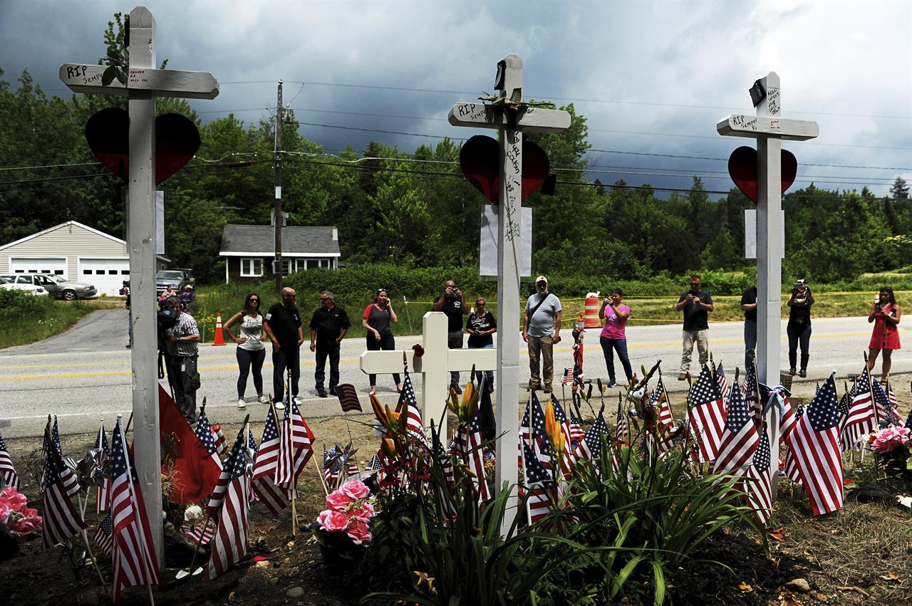 FILE - In this July 6, 2019, file photo, people view a memorial at the site where seven bikers riding with the Jarheads Motorcycle Club were killed in a collision last month in Randolph, N.H. The owners of the truck involved in a crash in New Hampshire in June 2019 that killed seven motorcyclists are facing charges of falsifying company records, federal prosecutors announced Friday, Feb. 26, 2021. Dunyadar Gasanov, also known as Damien Gasanov, 36, was indicted on charges of falsification of records, conspiracy to falsify records and making a false statement to a federal investigator, according to a statement from the U.S. attorney's office in Boston. (Paul Hayes/Caledonian-Record via AP)