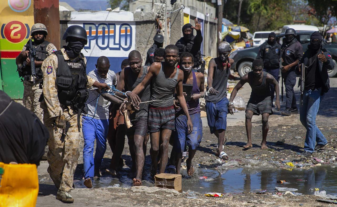 Recaptured inmates are led by police outside the Croix-des-Bouquets Civil Prison after an attempted breakout, in Port-au-Prince, Haiti, Thursday, Feb. 25, 2021. At least seven people were killed on Thursday after several inmates tried to escape from the prison, eyewitnesses told The Associated Press. (AP Photo/Dieu Nalio Chery).