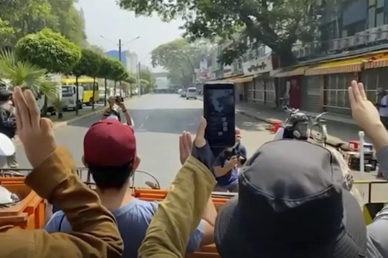 In this image made from video, anti-coup protesters flash the three-fingered salut at police, rear, in Yangon, Myanmar, Saturday, Feb. 27, 2021. Myanmar police on Saturday moved to clear anti-coup protesters from the streets of the country's biggest city Yangon. (AP Photo)