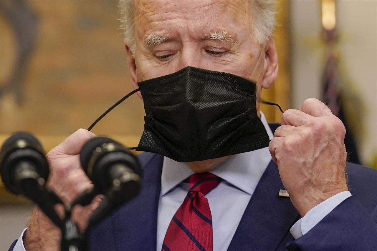 President Joe Biden removes his mask before speaking on the economy in the Roosevelt Room of the White House, Saturday, Feb. 27, 2021, in Washington. (AP Photo/Pablo Martinez Monsivais)