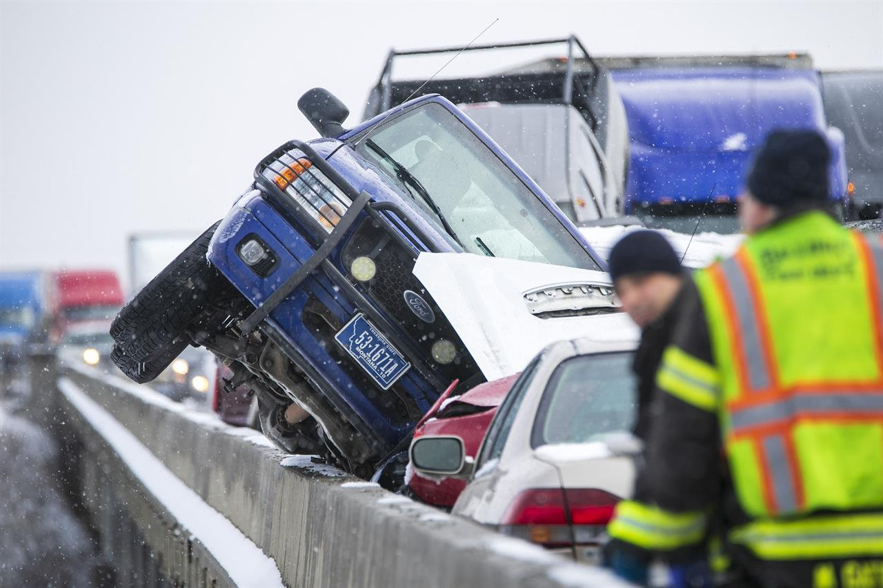 A vehicle leans the edge of the Yellowstone Bridge at the scene of a massive pileup that occurred on I-90 westbound Saturday, Feb. 27, 2021, on the Yellowstone Bridge near Lockwood, Mont. Dozens of vehicles crashed into each other Saturday on an icy interstate highway bridge over the Yellowstone River outside Billings, Montana, making the span appear like a wrecking yard with mashed cars and trucks.(Ryan Berry/The Billings Gazette via AP)