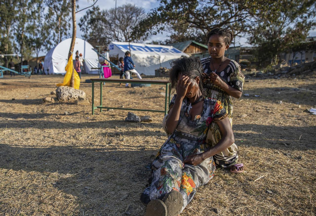 Almaz, 12, braids the hair of Zinabu at a center for people displaced by the recent conflict located in Meseret Primary School in Mekele, the capital of the Tigray region of northern Ethiopia Monday, Feb. 22, 2021. (Zerihun Sewunet/UNICEF via AP)