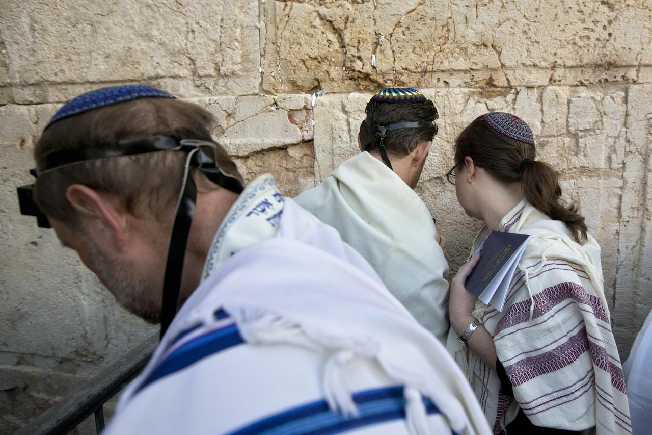 FILE - In this Feb. 25, 2016 file photo, American and Israeli Reform rabbis pray at the Western Wall, the holiest site where Jews can pray in Jerusalem's old city. Israel's Supreme Court on Monday, March 1, 2021, dealt a major blow to the country's powerful Orthodox establishment, ruling that people who convert to Judaism through the Reform and Conservative movements in Israel also are Jewish and entitled to become citizens. (AP Photo/Sebastian Scheiner, File)
