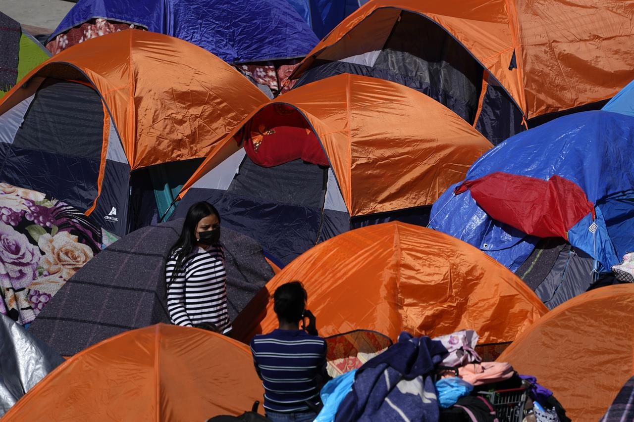 Tents used by migrants seeking asylum in the United States line an entrance to the border crossing, Monday, March 1, 2021, in Tijuana, Mexico. President Joe Biden is holding a virtual meeting with Mexican President Andrés Manuel López Obrador. Monday's meeting was a chance for them to discuss migration, among other issues. (AP Photo/Gregory Bull)