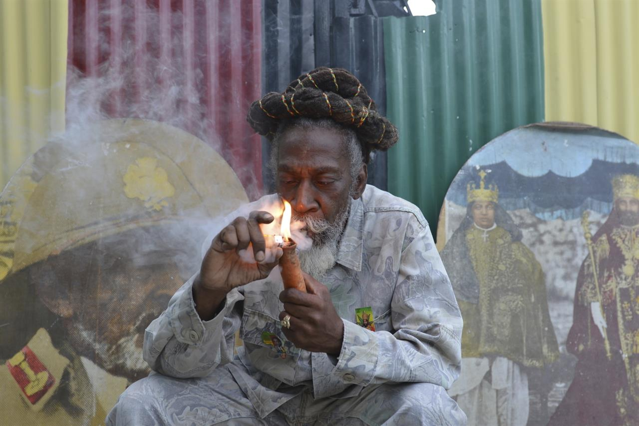 """FILE - In this Aug. 28, 2014 file photo, legalization advocate and reggae legend Bunny Wailer smokes a pipe stuffed with marijuana during a """"reasoning"""" session in a yard in Kingston, Jamaica. Wailer, a reggae luminary who was the last surviving member of the legendary group The Wailers, died on Tuesday, March 2, 2021, in his native Jamaica, according to his manager. He was 73. (AP Photo/David McFadden, File)"""