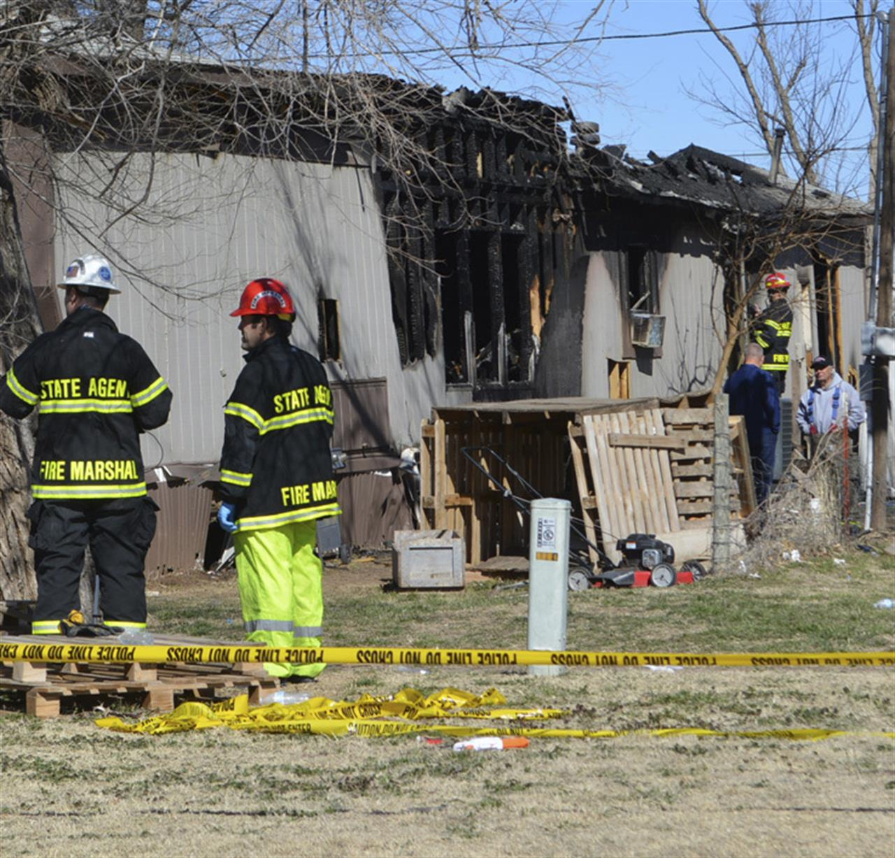 Investigators from the State Fire Marshal's office go over the site of a multi-fatality mobile home fire in Woodward, Okla., Wednesday, March 3, 2021. Officials say six people, including some children, are dead after a fire swept through the home. Fire Chief Todd Finley says one boy escaped the blaze early Thursday morning after a firefighter and a bystander were able to free him from a window. (Dawnita Fogleman/The Woodward News via AP)