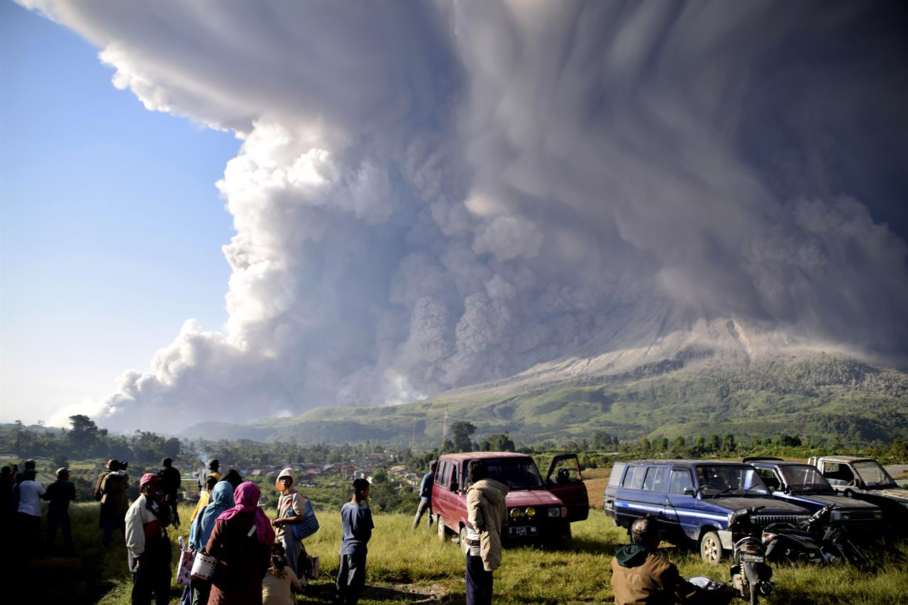 People watch as Mount Sinabung spews volcanic material during an eruption in Karo, North Sumatra, Indonesia, Tuesday, March 2, 2021. The 2,600-metre (8,530-feet) volcano erupted Tuesday, sending volcanic materials a few thousand meters into the sky and depositing ash on nearby villages. (AP Photo)