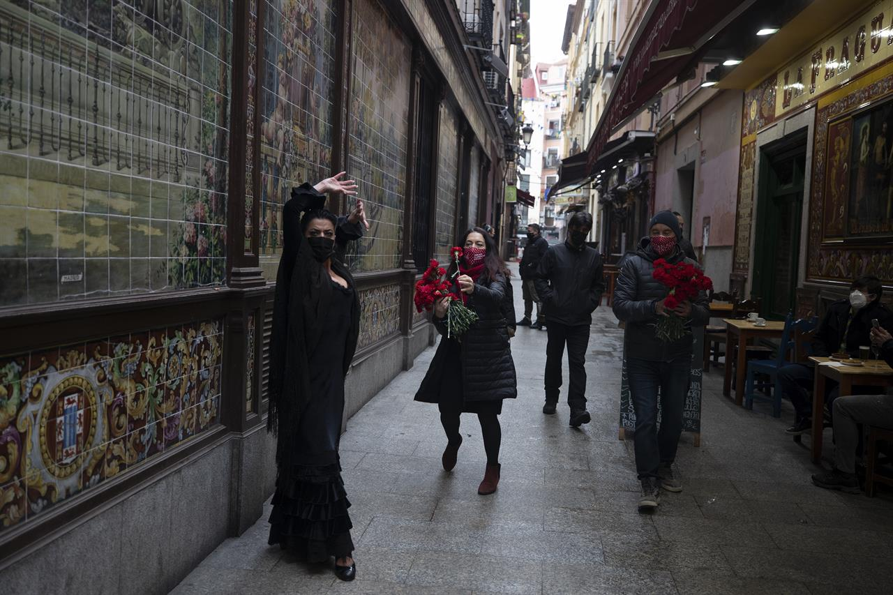Spanish Flamenco dancer Anabel Moreno dances outside the Villa Rosa Tablao flamenco venue as a woman comes to give her a rose during a protest in Madrid, Spain, Thursday March 4, 2021. The National Association of Tablaos protested outside the mythical Villa Rosa Tablao which has been forced to close permanently due to the covid pandemic. (AP Photo/Paul White)