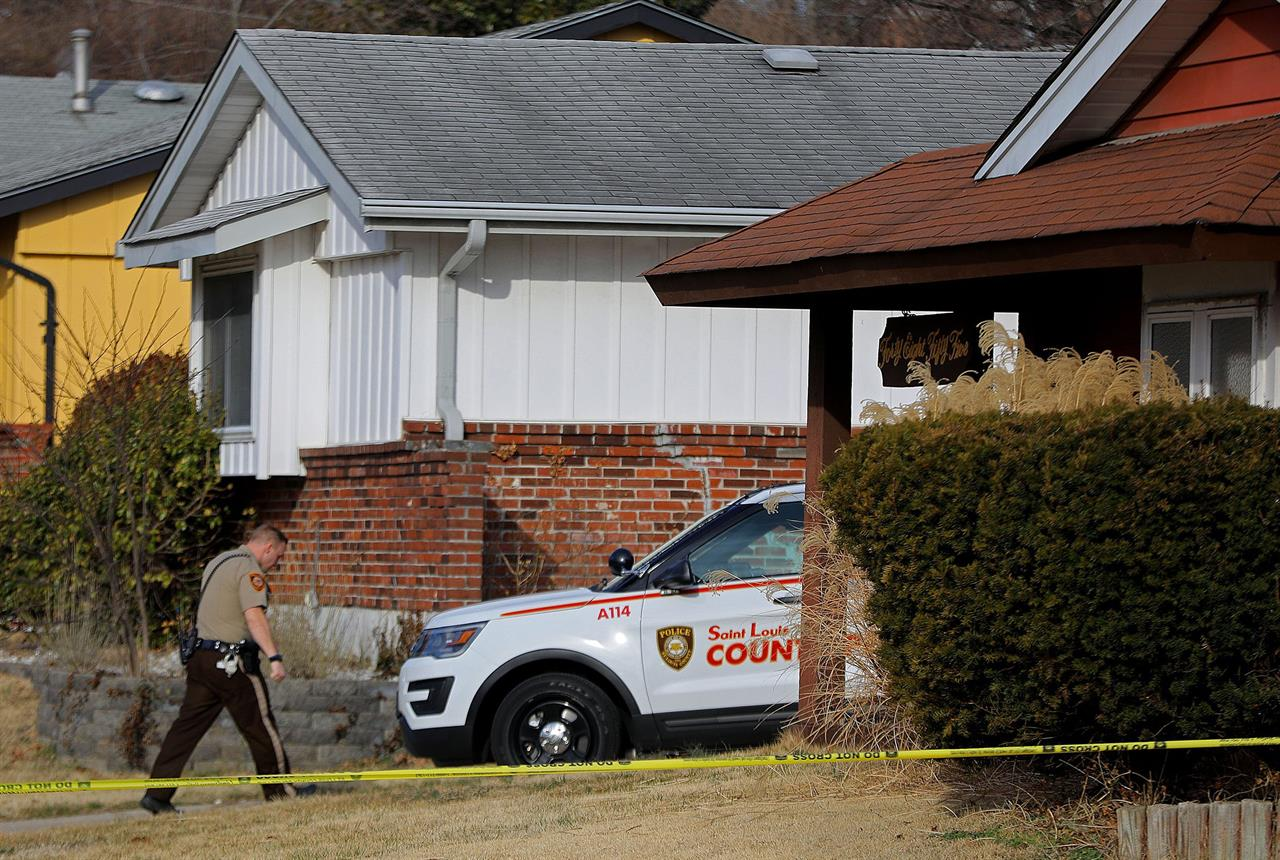 A St. Louis County police officer keeps watch over a home in the 4800 block of Lockwig Trail in north St. Louis County on Friday, March 5, 2021, where Bobby McCulley III allegedly shot and killed a woman and her two children. (Christian Gooden/St. Louis Post-Dispatch via AP)