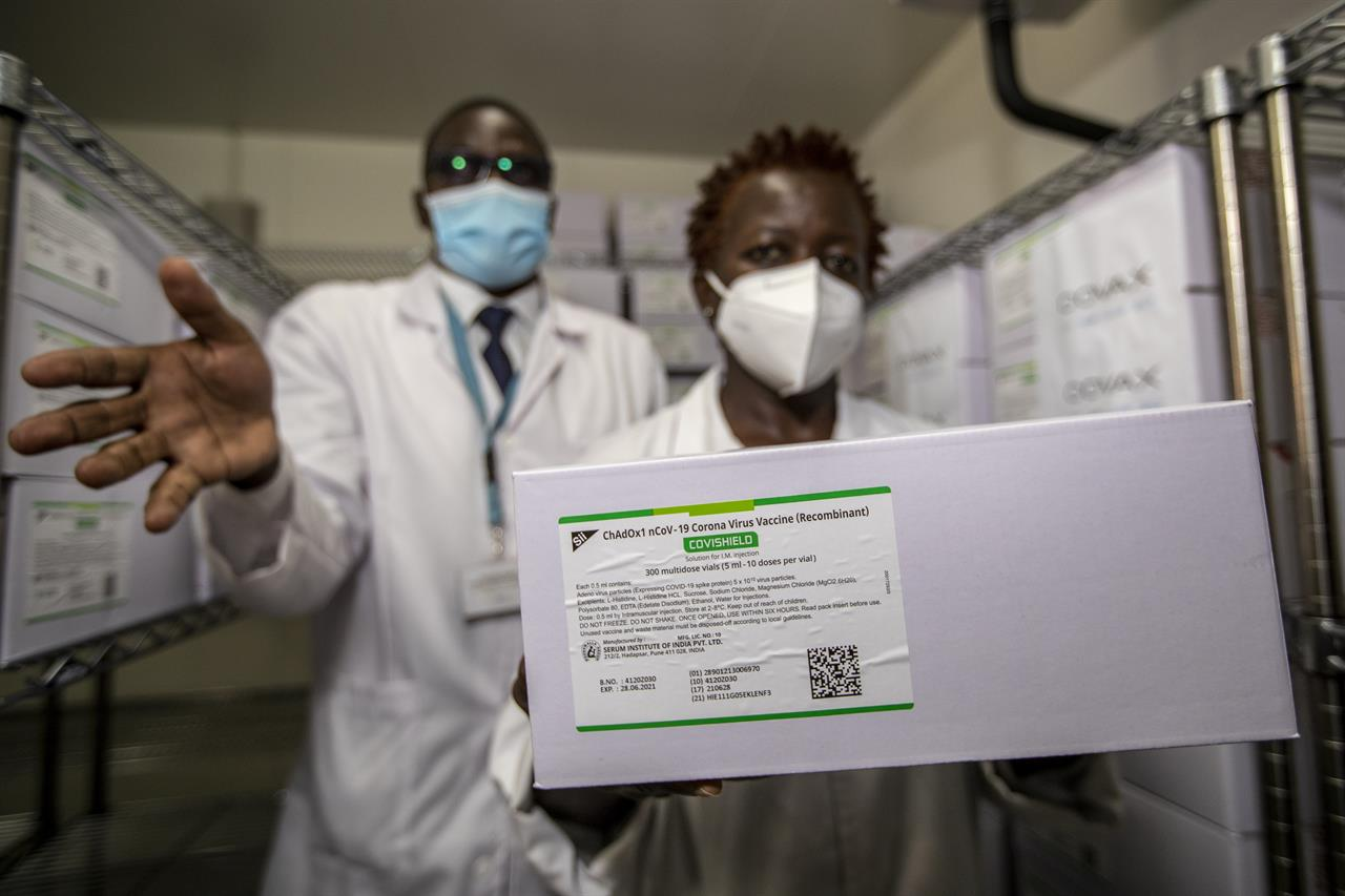 Technicians show a carton of AstraZeneca COVID-19 vaccine manufactured by the Serum Institute of India, inside a cold storage room at the central vaccine depot in Kitengela town on the outskirts of Nairobi, in Kenya Thursday, March 4, 2021. Around 1.02 million doses of the AstraZeneca COVID-19 vaccine arrived in the country on Wednesday as part of the COVAX facility. (AP Photo/Ben Curtis)