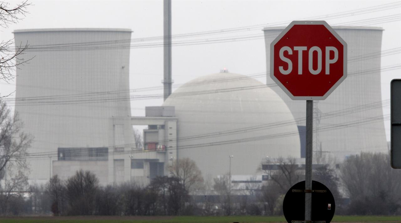 FILE - In this March 18, 2011 file photo, a traffic sign stands next to the nuclear power plant of Biblis, Germany. The German government said Friday it has agreed with four utility companies that they will receive a combined 2.4 billion euros ($2.9 billion) in compensation for the early shutdown of their nuclear power plants. (AP Photo/Michael Probst, file)