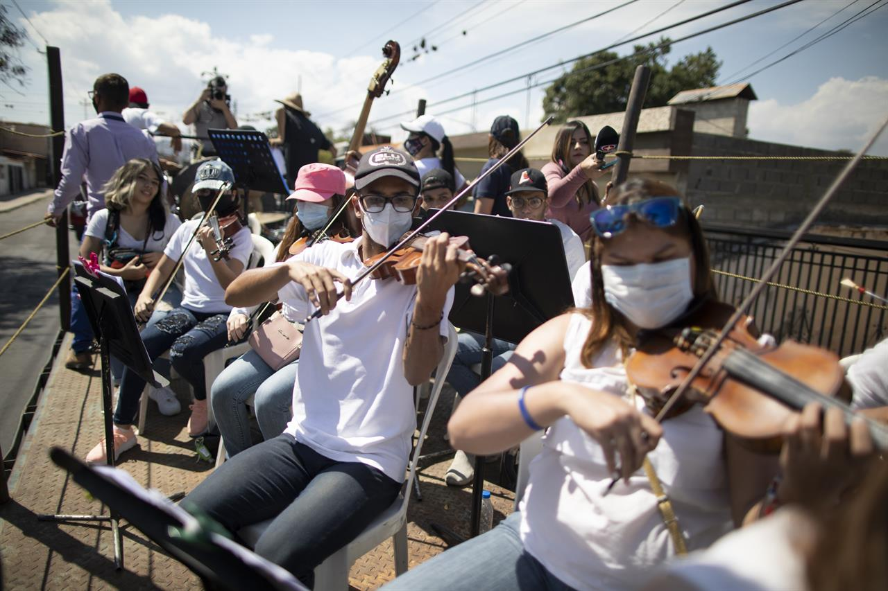"Wearing masks to curb the spread of the new coronavirus, musicians join pianist, composer and conductor Jose Agustin Sanchez on the bed of an eighteen-wheeler truck for a musical tour called ""Musical Disinfection,"" in Barquisimeto, Venezuela, Thursday, March 4, 2021. Sanchez, who last year started playing what he calls his ""Musical Vaccine"" for COVID patients, is now joined by other musicians as they ride through the city playing his original compositions for anybody that wants to listen. (AP Photo/Ariana Cubillos)"