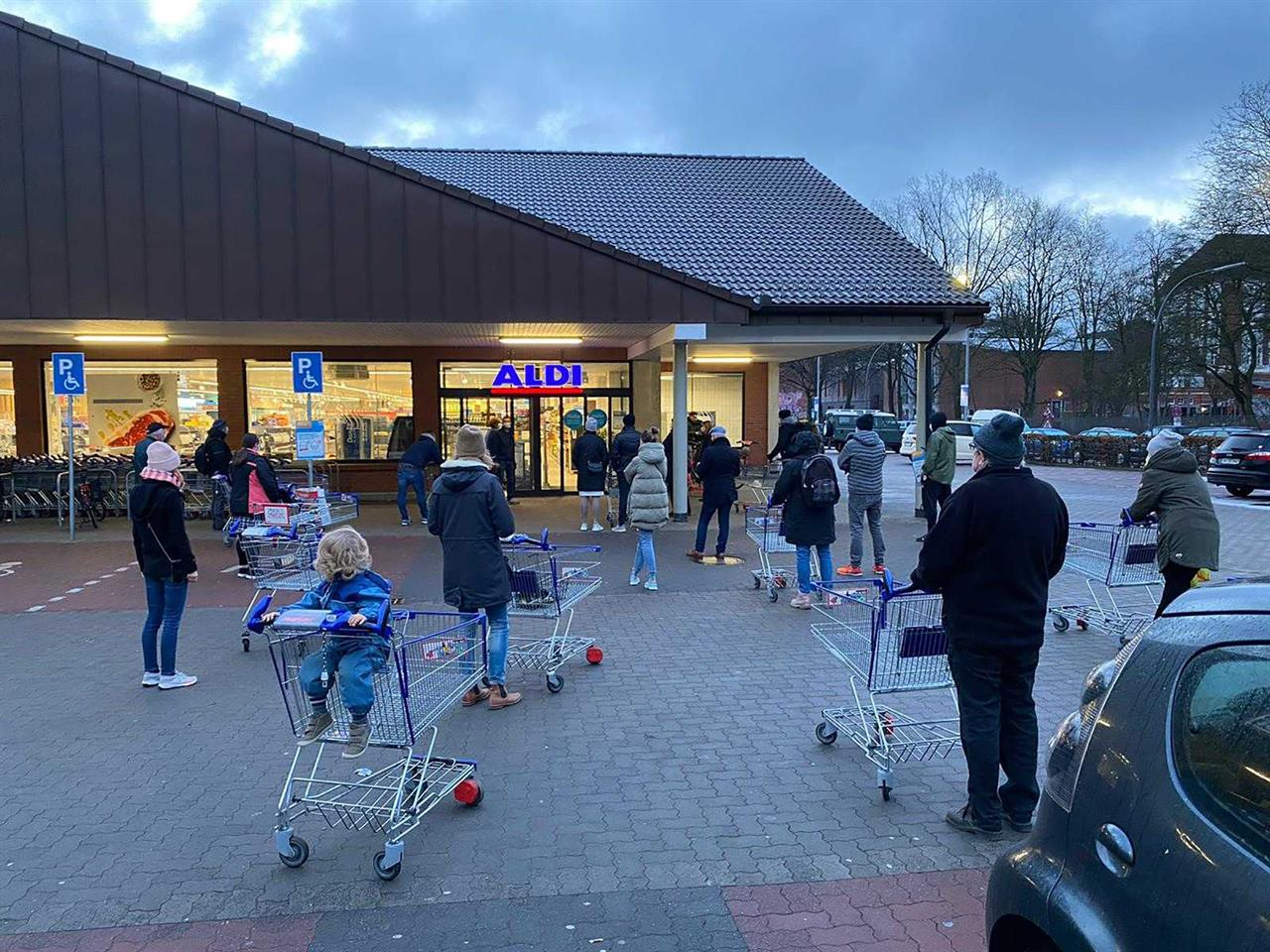 Customers wait for the opening of a branch of the German discounter 'Aldi' in Hamburg, Germany, Saturday, March 6, 2021. From Saturday the discounter offers new coronavirus, COVID-19, quick tests for sale. (Haller/dpa via AP)