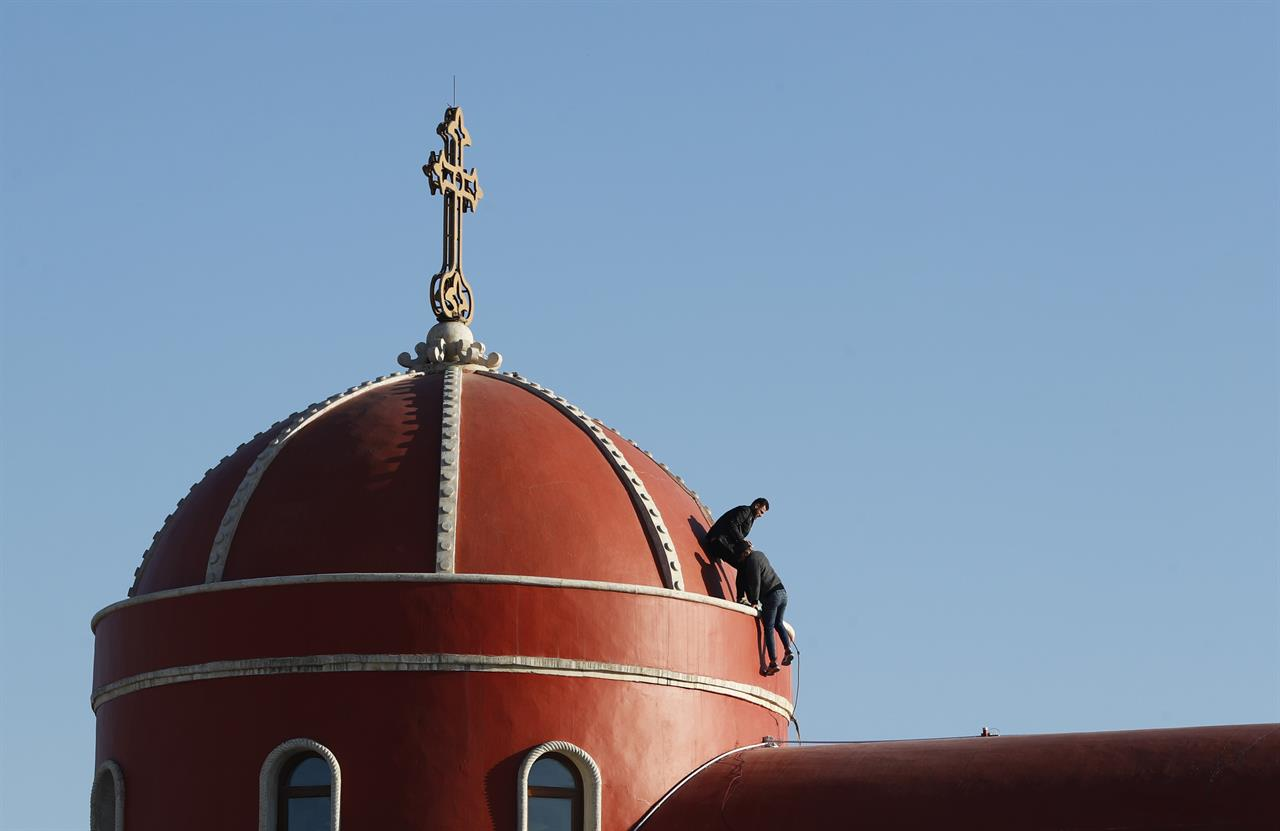 Iraqi Christians clean the the roof of the Church of the Immaculate Conception in Qaraqosh, Iraq, Tuesday, Feb. 23, 2021. Pope Francis will visit the church during his historic trip to Iraq.   Damaged during the Islamic State reign of terror, the church's tragedy mirrored that of its Christian community which was devastated by the group.  (AP Photo/Hadi Mizban)