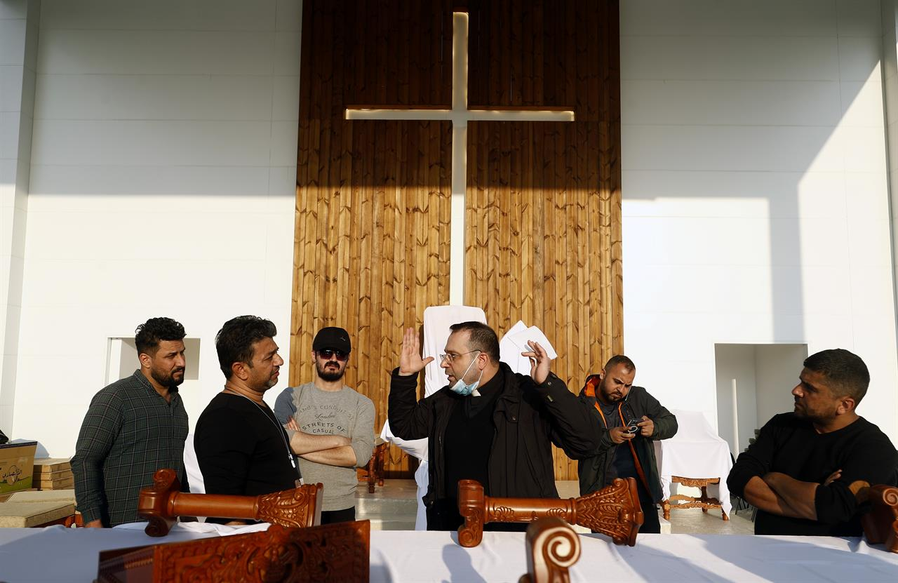 Iraqi Christians talk during preparations before Pope Francis visit at the main stadium in Irbil, Iraq, Saturday, March 6, 2021. Earlier today Francis met privately with the country's revered Shiite leader, Grand Ayatollah Ali al-Sistani. (AP Photo/Hadi Mizban)
