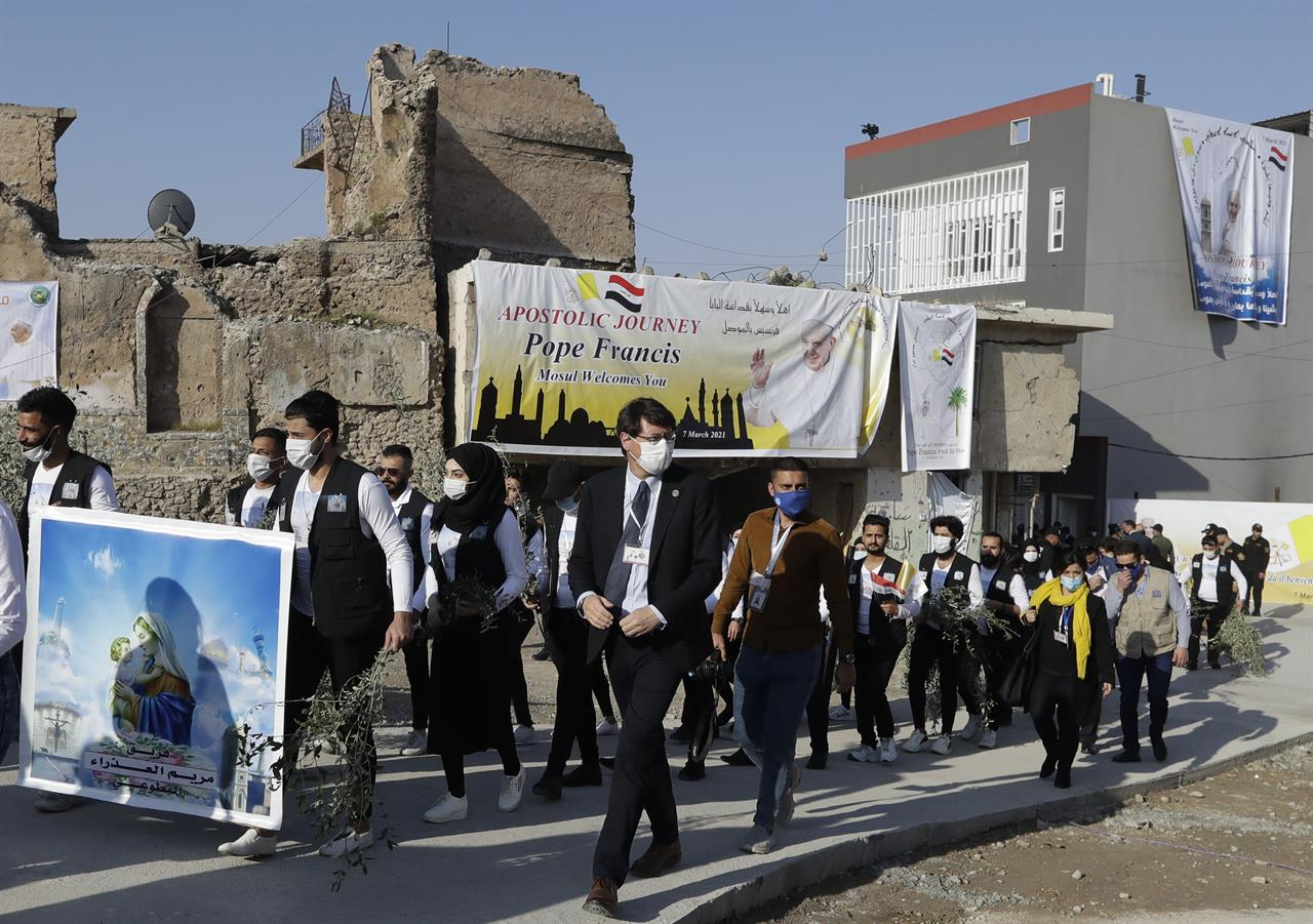 Surrounded by shells of destroyed buildings people arrive to join Pope Francis who will pray for the victims of war at Hosh al-Bieaa Church Square, in Mosul, Iraq, once the de-facto capital of IS, Sunday, March 7, 2021. The long 2014-2017 war to drive IS out left ransacked homes and charred or pulverized buildings around the north of Iraq, all sites Francis visited on Sunday. (AP Photo/Andrew Medichini)