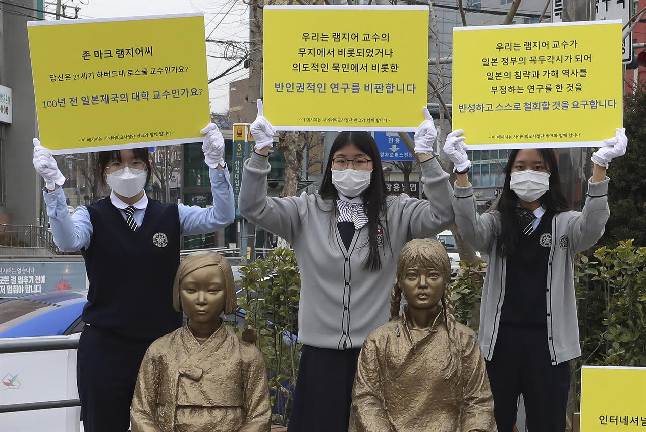 "In this Feb. 25, 2021, photo, high school students hold up banners to protest a recent academic paper by Harvard University professor J. Mark Ramseyer, behind statues symbolizing wartime sex slaves in Seoul, South Korea. The signs read: ""J. Mark Ramseyer, are you a 21st century professor at Harvard? Are you a university professor in the Japanese Empire 100 years ago? We criticize anti-human rights research."" (Lee Jung-hoon/Yonhap via AP)"
