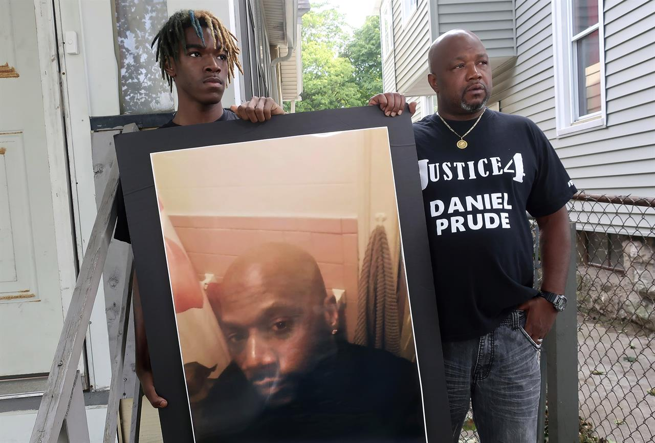 CORRECTS TO BROTHER NOT UNCLE OF DANIEL PRUDE - FILE - In this Sept. 3, 2020, file photo, Joe Prude, right, brother of Daniel Prude, and Daniel's nephew Armin, stand with a picture of Daniel Prude in Rochester, N.Y. In a decision announced Tuesday, Feb. 23, 2021, a grand jury voted not to charge officers shown on body camera video holding Daniel Prude down naked and handcuffed on a city street last winter until he stopped breathing. (AP Photo/Ted Shaffrey, File)