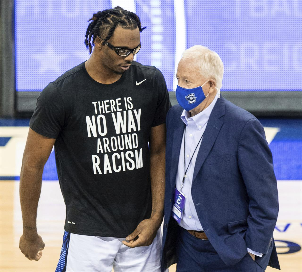 In this March 6, 2021, photo, Creighton's Denzel Mahoney, left, talks to Creighton athletic director Bruce Rasmussen during Senior Day festivities, in Omaha, Neb. Creighton announced Monday, March 8, 2021, it has lifted Greg McDermott's suspension for making racially insensitive remarks to his players after a game last week. Noting McDermott's public apologies and difficult discussions with his players and others, Rasmussen said the coach has shown a willingness to learn from the mistake. (Chris Machian/Omaha World-Herald via AP)