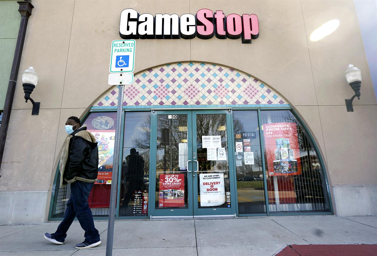 """FILE - In this Jan. 28, 2021 file photo, a pedestrian passes a GameStop storefront in Dallas. GameStop shares jumped around 12% in premarket trading Monday, March 8 after the video game retailer appointed a committee it said would aim to """"transform GameStop into a technology business.""""  (AP Photo/LM Otero, File)"""
