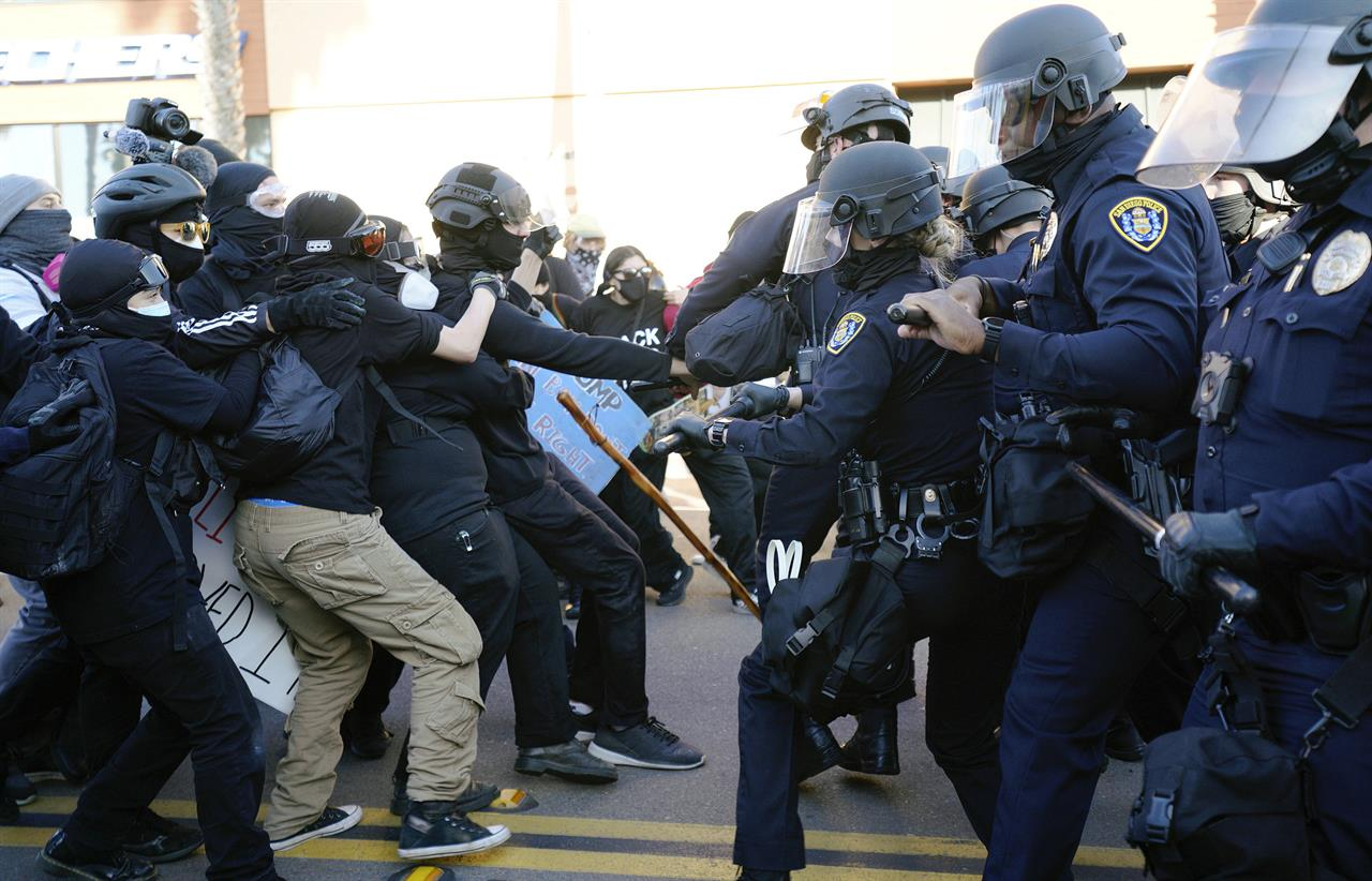 San Diego police clash with protesters after a gathering was declared an unlawful assembly, Saturday, Jan. 9, 2021, in San Diego. Supporters of President Donald Trump clashed with counter-protesters in San Diego on Saturday, prompting police to declare the gathering an unlawful assembly because of acts of violence. (Nelvin C. Cepeda/The San Diego Union-Tribune via AP)