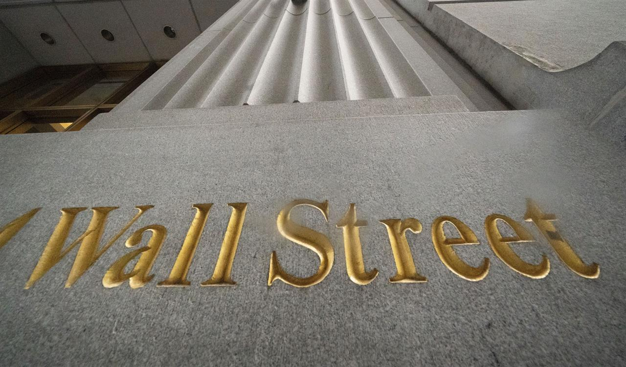 FILE - In this Nov. 5, 2020 file photo, a sign for Wall Street is carved in the side of a building.  Stocks are opening higher on Wall Street led by gains in Big Tech companies. The S&P 500 was up 0.4% early Wednesday, March 31, 2021.  (AP Photo/Mark Lennihan, File)